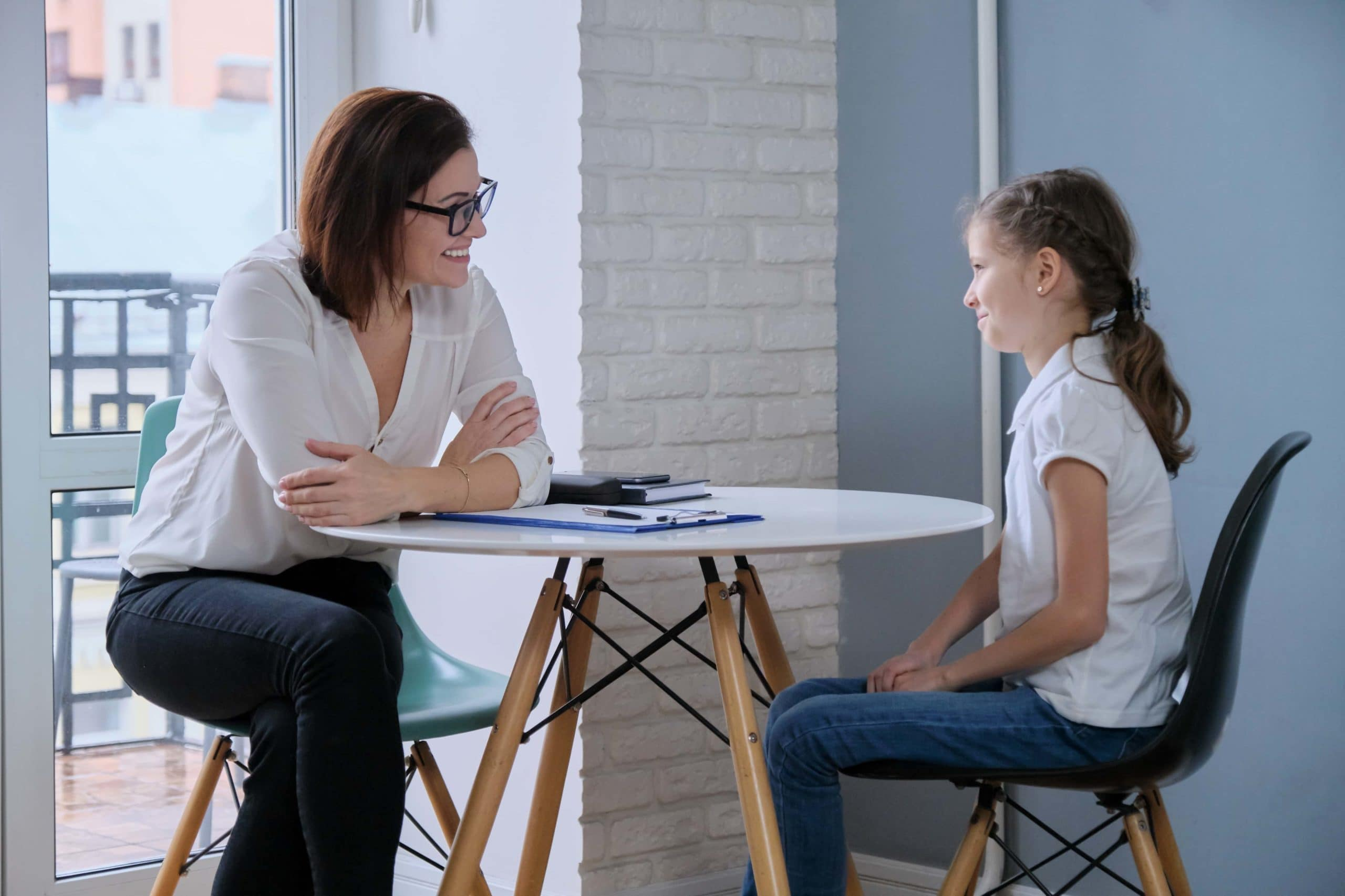 Communication session of school psychologist and girl 9, 10 years. Child tells psychotherapist his experiences, mental health of children