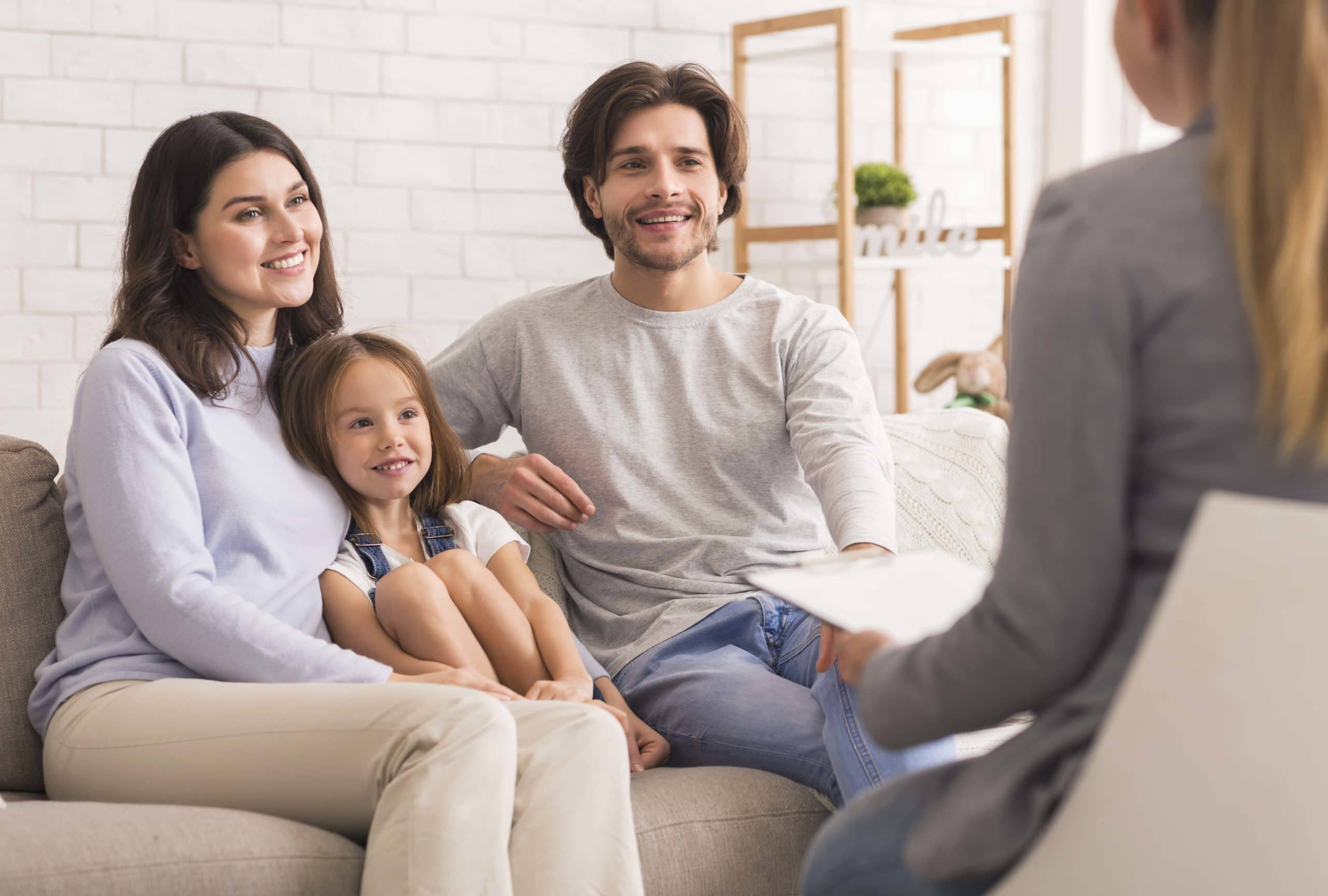 Happy Parents With Little Daughter Sitting Together At Psycholigist's Office After Successful Family Therapy